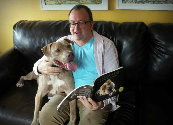 Photo of Ken Foster reading to his pitbull
