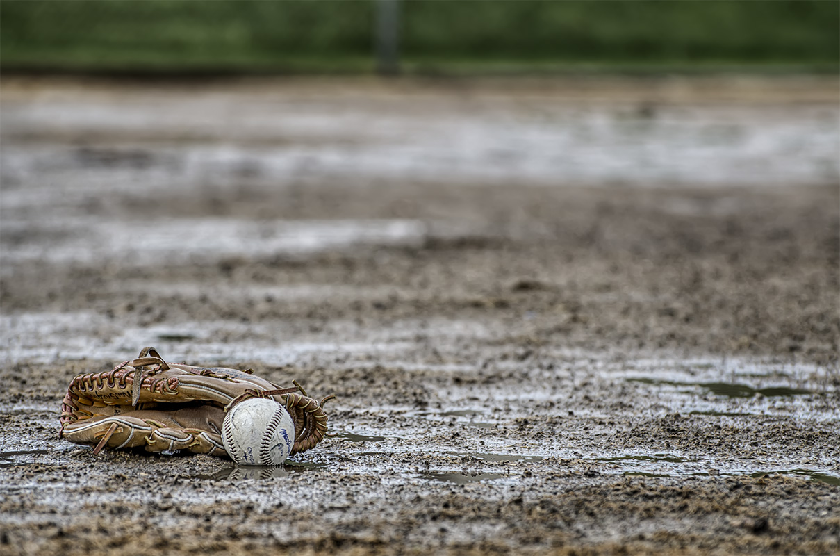 photo of glove lying on muddy baseball field