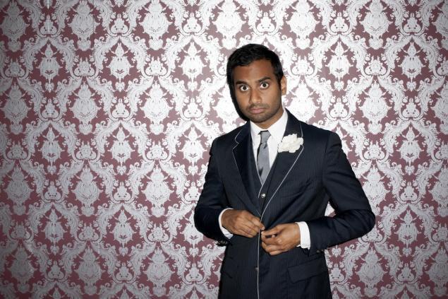 Author Aziz Ansari posing next to patterned wallpaper photo