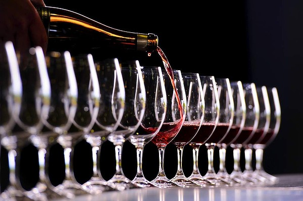 Wine being poured into glasses photo
