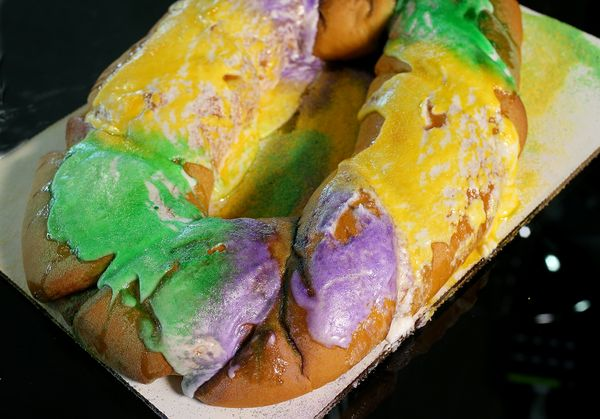Photo of a slice of King Cake with multi-color icing